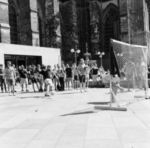 Street performers letting a kid kick a ball at him